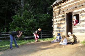 Lori photographs young interpreters playing with clay marbles in front of the reconstructed slave cabin, while I look on.