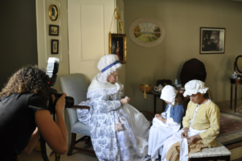 Lori photographs a sewing scene with two young interpreters and Mary Wiseman, who portrays Martha Washington. The real Martha Washington taught young slave girls to sew the clothing that was worn by other slaves at Mount Vernon.