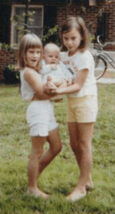 My sister Karen and I hold our baby sister, Sherri. I'm the tall one.